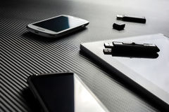 2 Business Mobiles With Reflections And An USB Drive Lying Next To A Blank Tablet With USB Drive On Top, All Above A Carbon Layer Royalty Free Stock Images