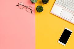 Business mockup with smartphone with black copyspace screen, succulent flowers, glasses, pink laptop, pastel pink and yellow backg. Round. Copyspace royalty free stock images