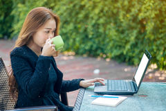 Business Modern woman. With information check from the laptop and drink coffee in the morning Royalty Free Stock Images