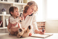 Business mom and baby boy. Beautiful business mom is talking on the mobile phone and taking notes while spending time with her cute baby boy at home Royalty Free Stock Photography