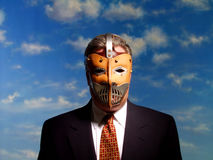 Business Monster. Businessman wearing a frightening mask against a blue sky Stock Photography