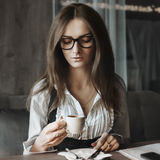 Business mood and coffee. Fashion art portrait of young pretty business woman in restaurant Royalty Free Stock Photography