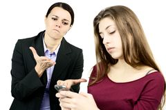 Business mother angry with daughter addicted to cell phone Royalty Free Stock Photo