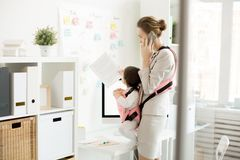 Childcare and work. Business mother with her daughter in baby carrier standing in front of office noticeboard with working reminders, reading them and talking by stock photo