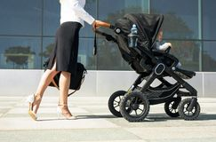 Business mother pushing baby on the way to work Royalty Free Stock Images