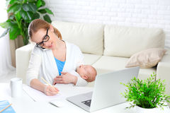 Business  mother works at home via Internet with newborn baby Stock Photo