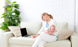 Business  mother works at home via Internet with newborn baby Stock Photography