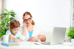 Business  mother works at home via the Internet with their child Stock Photos
