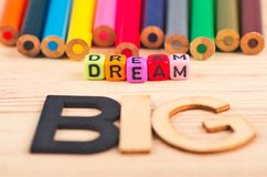 Colorful cubes with words DREAM BIG on wooden desk royalty free stock image