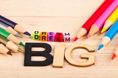 Colorful cubes with words DREAM BIG on wooden desk royalty free stock images