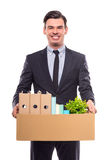 Business moving in office. Young happy businessman with box for moving into a new office. Studio shot, isolated on a white background stock photography