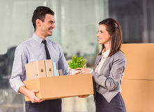 Business moving in office. Young happy businessman and a business women with boxes for moving into a new office stock images