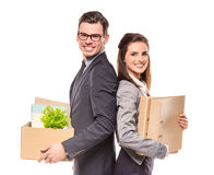 Business moving in office. Young happy businessman and a business women with boxes for moving into a new office. Studio shot, isolated on a white background Royalty Free Stock Photography