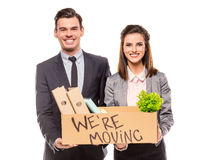 Business moving in office. Young happy businessman and a business women with boxes for moving into a new office. Studio shot, isolated on a white background stock photography
