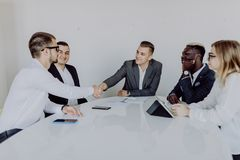 Business multiethnic team, handshake. Agreement at meeting. Busy people work in office. Copy space on the screen stock images