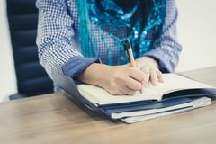 Muslim woman hand working and writing on a notepad stock photography
