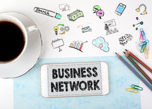 Business network concept. Mobile phone and coffee cup on a white office desk Royalty Free Stock Photography