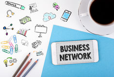 Business network concept. Mobile phone and coffee cup on a white office desk Royalty Free Stock Photos