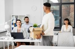 Office workers looking at colleague quitting job. Business, new job and quit concept - happy smiling office workers looking at indian male colleague with box of royalty free stock image