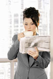 Business News. Businesswoman in grey suit enjoys coffee and newspaper Royalty Free Stock Photography