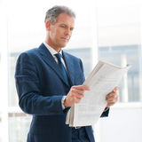 Business news. Mature business man reading news in the office Royalty Free Stock Photography
