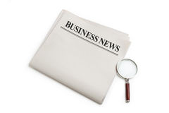 Business News and magnifying glass Stock Images
