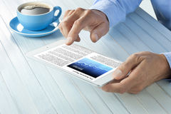 Business News Tablet Hands. A person reading the morning business news on a tablet computer with a cup of coffee Royalty Free Stock Images