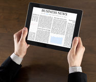 Business News On Tablet PC. Businessman hands are holding the touch screen device with business news on screen Stock Images