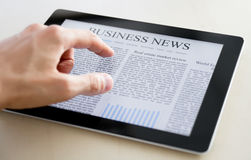 Business News On Tablet PC. Man hands are pointing on touch screen device with business news Stock Photos