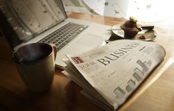 Daily business newspaper. At breakfast beside a coffee mug, muffin and laptop