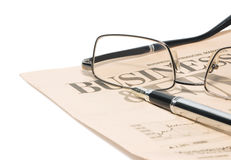 Business newspaper. With glasses and pen Stock Image