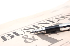 Business newspaper. With a pen on the white fon Stock Images