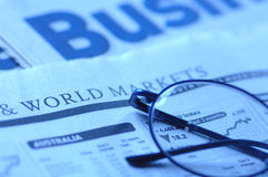 Business newspaper. Glasses on top of the newspaper Royalty Free Stock Photo