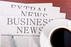 Business newspaper and  cup of coffee Stock Photos