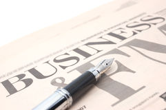 Business newspaper and pen. Business newspaper with a pen on the white fon Royalty Free Stock Images