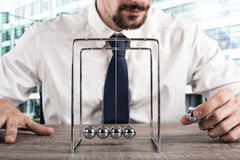 Business Newtons cradle. Businessman plays with the pendulum of Newtown balls Stock Photography