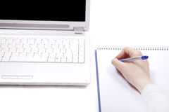 Business notebook with laptop and pen in hand. Royalty Free Stock Photo