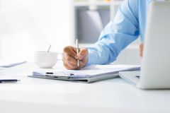 Business notes. Close-up of male hand making notes in office Royalty Free Stock Image