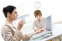 Business notes. Senior businesswoman and young assistant working  in office Stock Photos