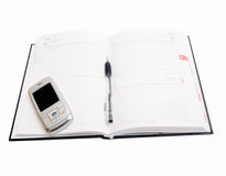 Business Objects - Agenda open met cellphone Stock Foto