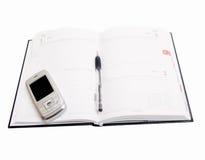 Business Objects - diario aperto con il cellulare Fotografia Stock