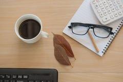 Business Objects nell'ufficio caffè e tastiera della tazza sulla tavola di legno Immagini Stock