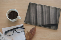 Business Objects no escritório café e tabuleta do copo na tabela de madeira Fotos de Stock Royalty Free
