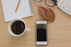 Business Objects no escritório café e telefone do copo na tabela de madeira Imagens de Stock Royalty Free