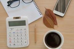 Business Objects no escritório café e telefone do copo na tabela de madeira Fotografia de Stock Royalty Free