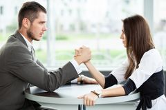 Business and office concept - businesswoman and businessman arm wrestling during meeting in office. stock image
