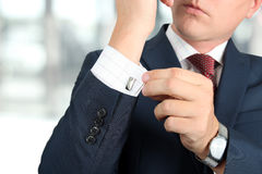Business and office concept -  elegant young fashion  buisness man in  a blue/navy suit touching at his cufflinks.  Stock Photo