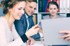 Business and office concept - smiling business team looking at clipboard. Teamwork and partnership. Business and office concept - smiling business team looking Stock Image
