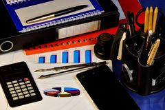 Business office is growing steadily up-indicates the chart. Calculator, smartphone, red folder with important reports and work. Plan, pen and notebook for stock images
