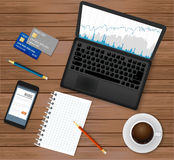 Business office workplace.Top view. Laptop with financial graph on screen,  coffee cup, smartphone, credit cards,notepad. Business office workplace.Top view Royalty Free Stock Images